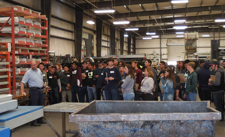 Students gather to view a piece of machinery